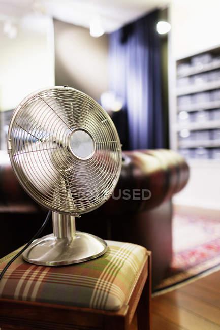 Вентилятор на стуле в магазине одежды — стоковое фото