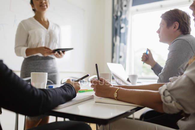 Деловая женщина объясняет коллегам в зале заседаний — стоковое фото