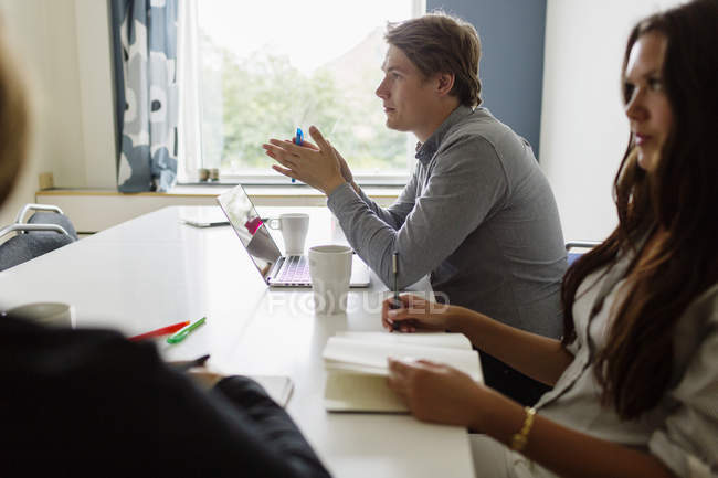 Coworkers discussing by table at office — Stock Photo