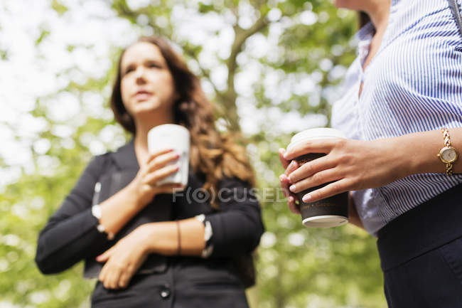 Businesswoman holding coffee outdoors — Stock Photo