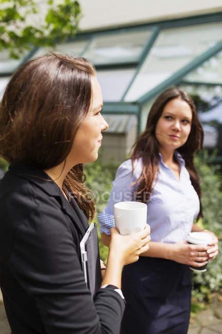 Businesswomen holding coffee — Stock Photo