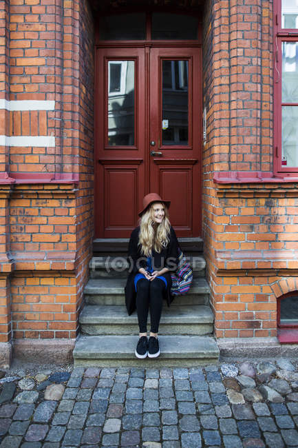 Woman looking away while sitting on steps — Stock Photo