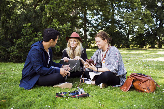Freelancers discussing while sitting at park — Stock Photo