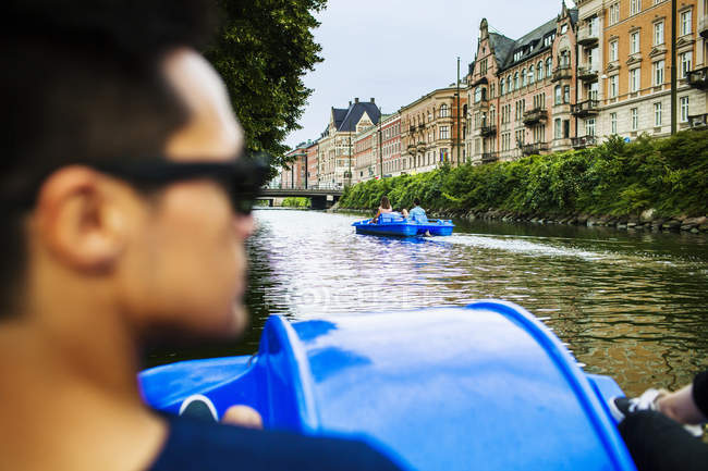 Man pedaling boat on river in city — Stock Photo