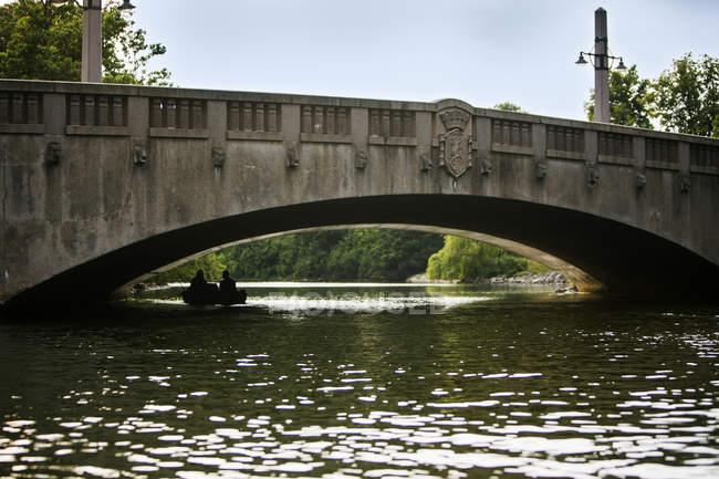 Friends pedaling boat below arch bridge — Stock Photo