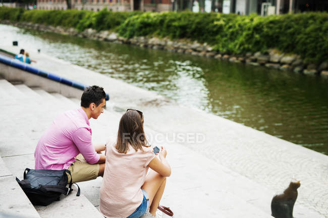 Friends sitting on steps by river — Stock Photo