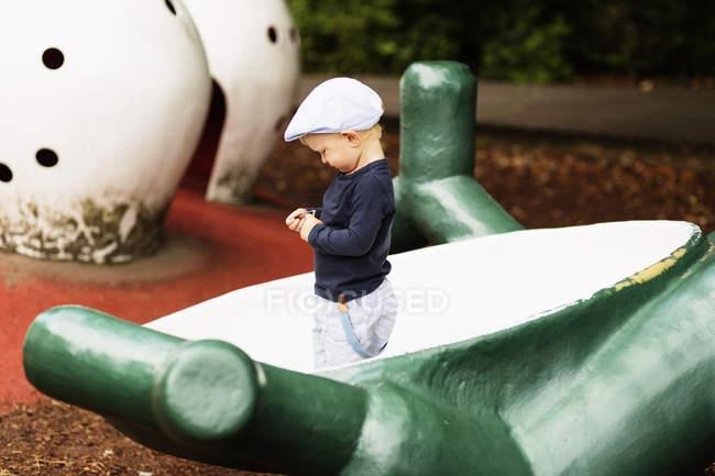 Хлопчик стоїть на структуру на майданчику — стокове фото