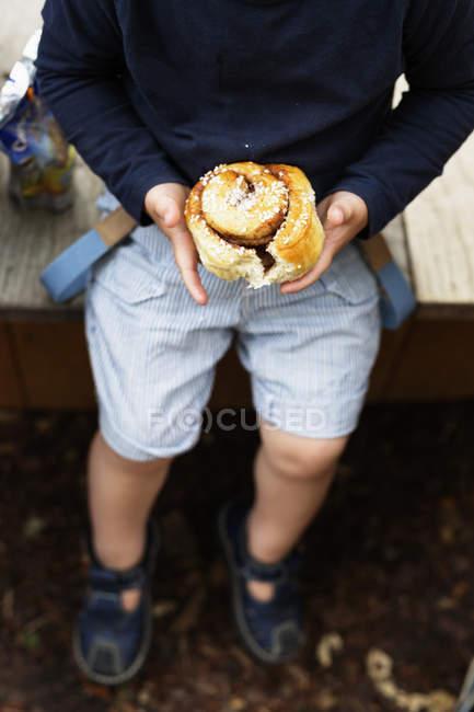 Мальчик держит выпечку в парке — стоковое фото