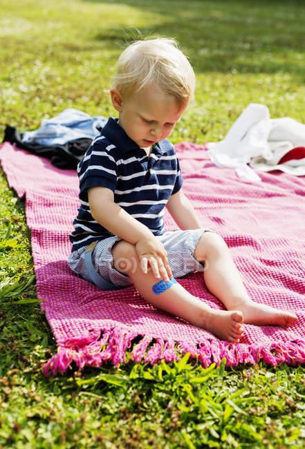 Boy with bandage on leg sitting on picnic blanket — Stock Photo