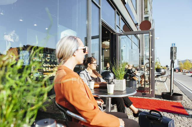 Businesswomen looking away while sitting at cafe — Stock Photo