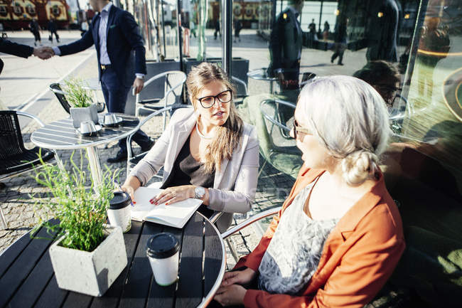 Businesswomen discussing at cafe table — Stock Photo