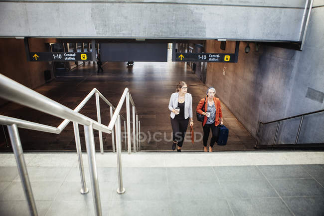 Businesswomen moving up steps at railroad station — Stock Photo