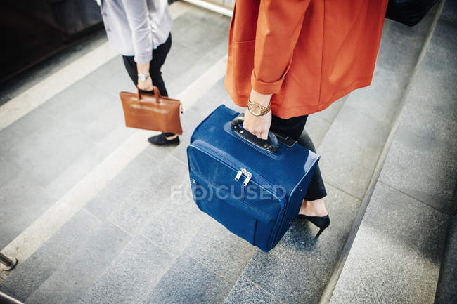 Businesswomen with luggage moving down steps — Stock Photo