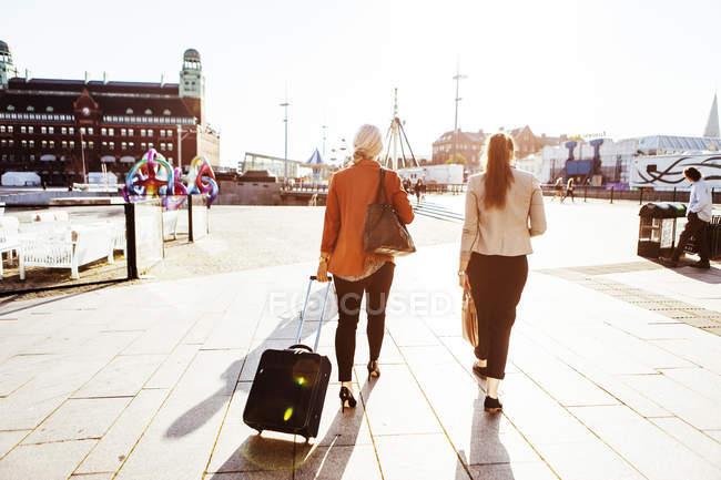 Mujeres de negocios con equipaje caminando por la calle de la ciudad - foto de stock