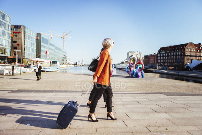 Businesswoman with luggage walking on city street — Stock Photo
