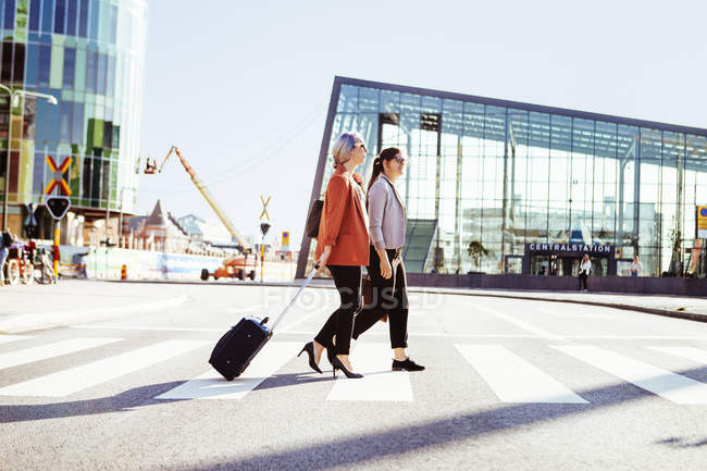 Businesswomen walking outside railroad station — Stock Photo