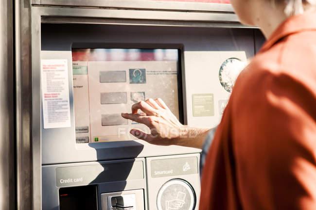 Businesswoman using ticket machine — Stock Photo