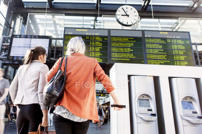 Businesswomen looking at arrival departure board — Stock Photo