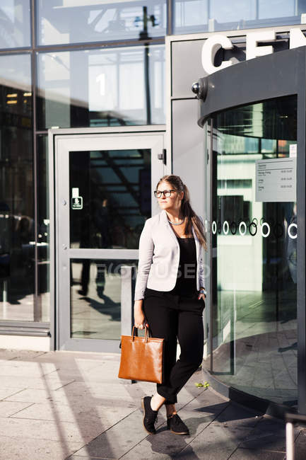 Businesswoman standing outside railroad station — Stock Photo