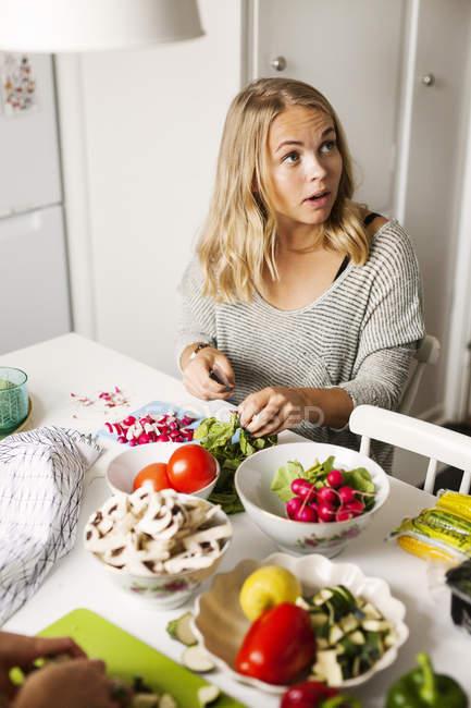 Женщина смотрит в сторону во время резки овощей — стоковое фото