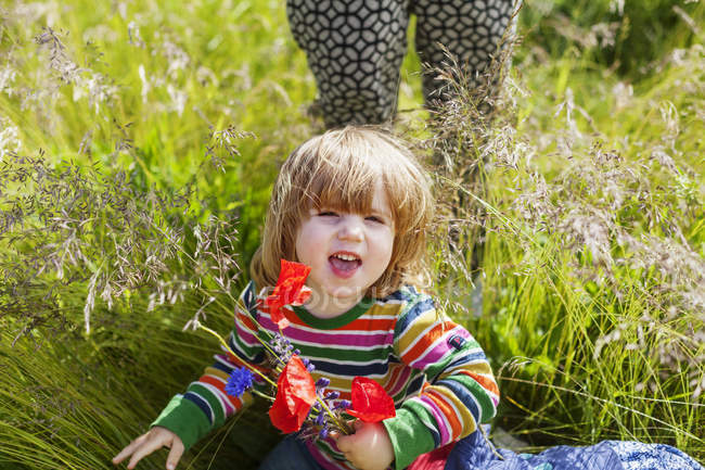 Girl holding flowers on grassy field — Stock Photo