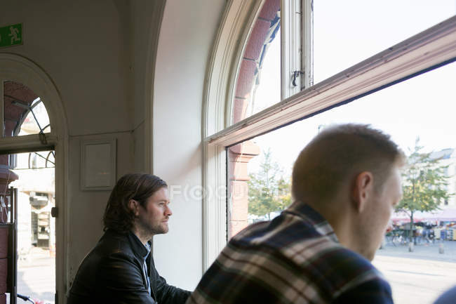 Men looking through window — Stock Photo