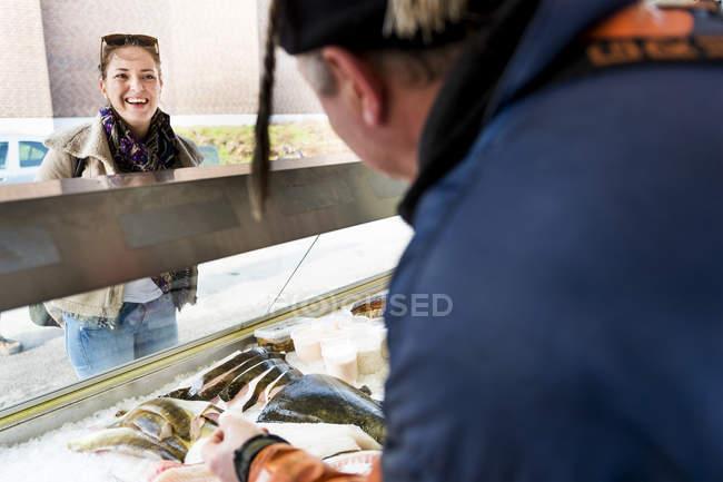 Female customer looking at fisherman - foto de stock