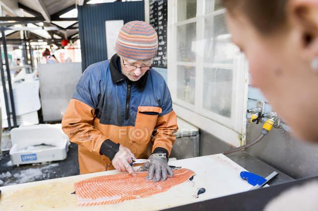 Женщина смотрит на взрослого рыбака — стоковое фото