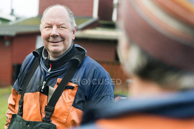Рыбак беседует с коллегой на открытом воздухе — стоковое фото