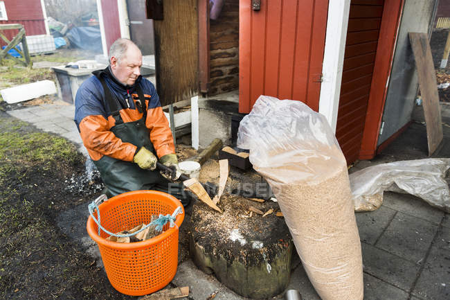 Рыбак режет дрова камином — стоковое фото