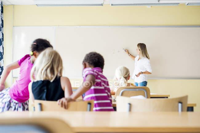 Lehrer und Kinder im Matheunterricht — Stockfoto