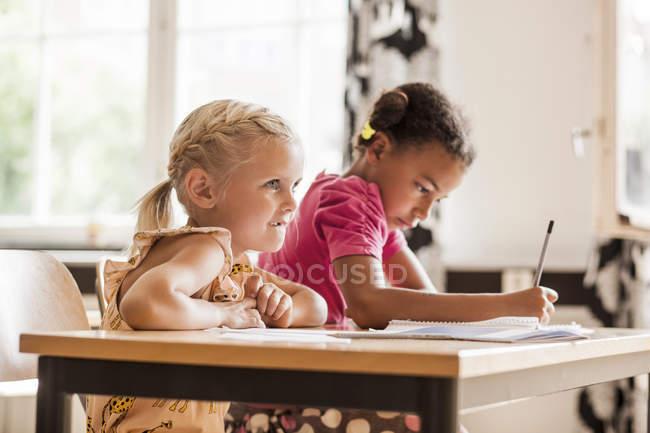 Filles de prendre des notes en classe — Photo de stock