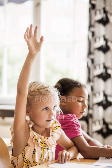 Girl raising hand in classroom — Stock Photo