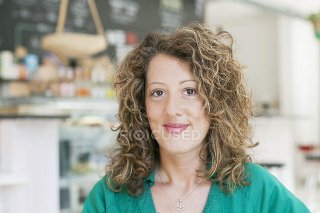 Woman looking at camera in coffee shop — Stock Photo