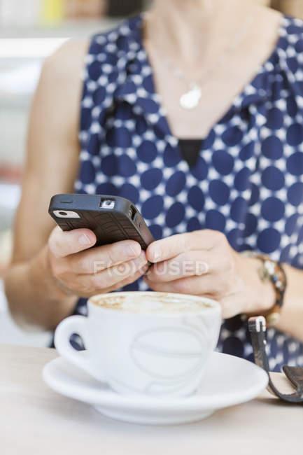 Mulher usando telefone celular com café — Fotografia de Stock