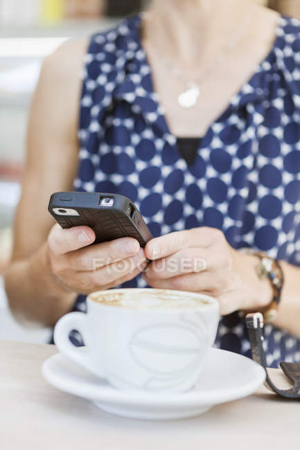 Woman using mobile phone with coffee — Stock Photo