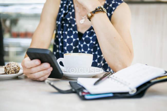 Mujer usando teléfono móvil con café - foto de stock