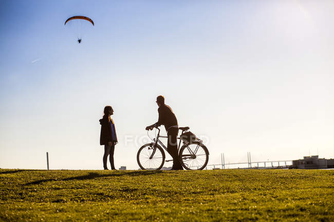 Couple watching paraglider — Stock Photo