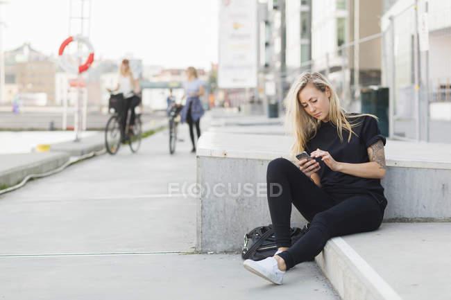 Studente che utilizza il telefono cellulare su gradini — Foto stock