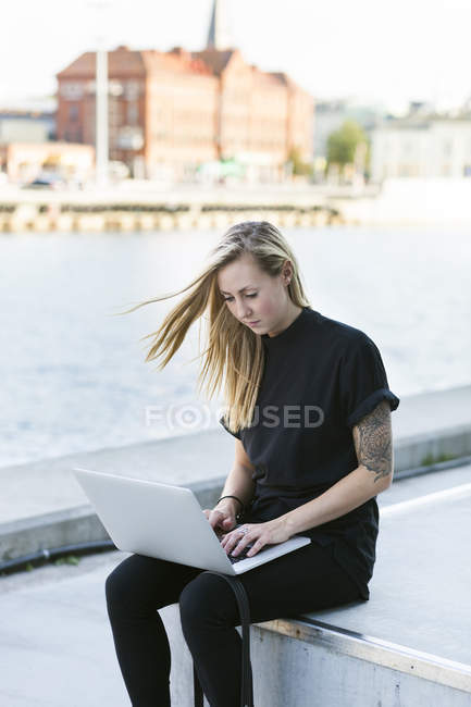Student using laptop by river — Stock Photo
