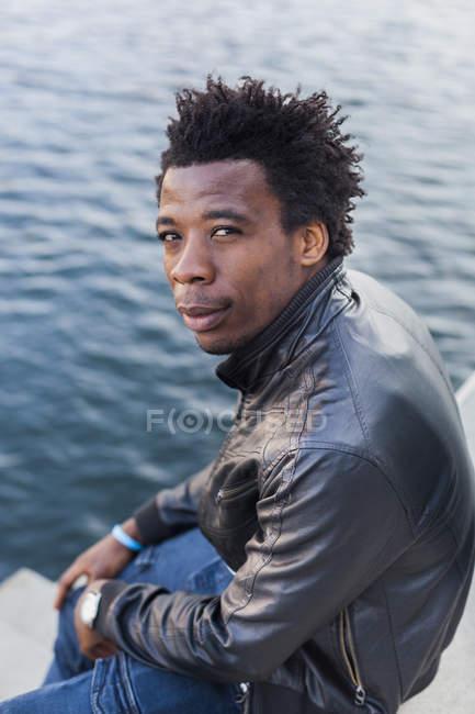 Estudiante universitario seguro sentado junto al río - foto de stock