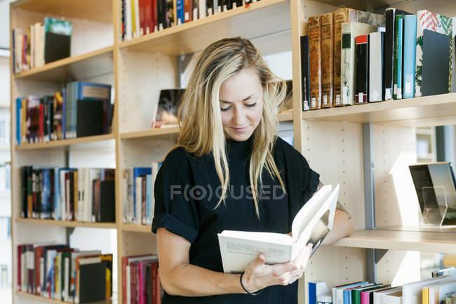 Femme lisant le livre tout en se penchant sur l'étagère — Photo de stock