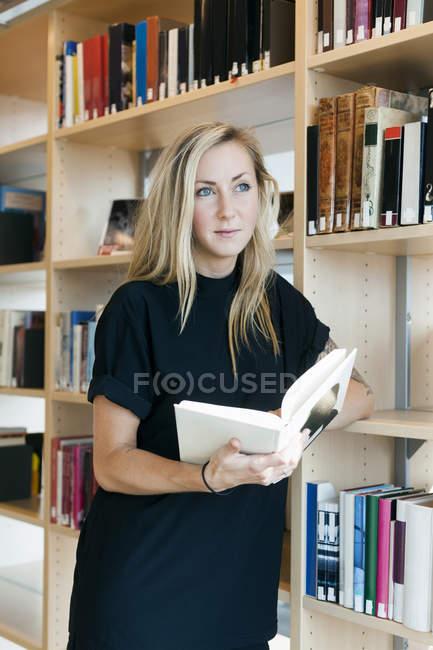 Étudiant à la recherche de suite tout en tenant le livre — Photo de stock