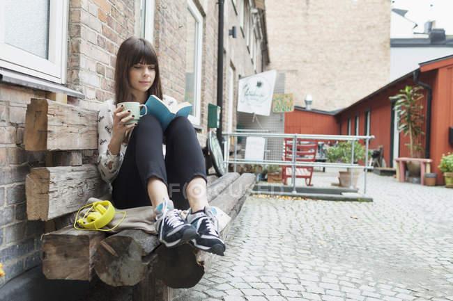 Frau Buch Kaffeetasse mit gedrückter — Stockfoto