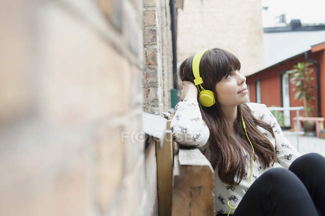 Woman looking away while listening music — Stock Photo