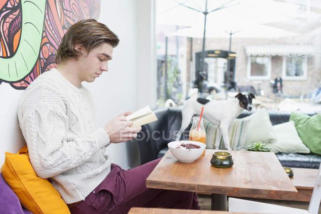Libro di lettura dell'uomo al café — Foto stock