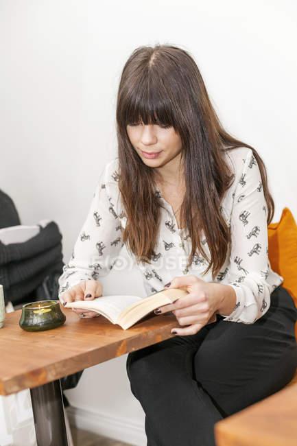 Frau Lesebuch am Café-Tisch — Stockfoto