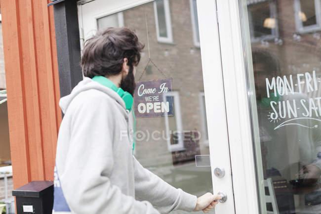 Людина, що відкриття дверей кафе — стокове фото