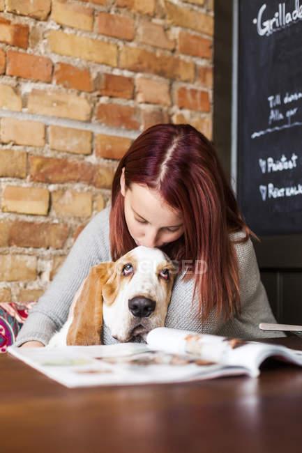 Junge Frau küsst Basset Hound — Stockfoto