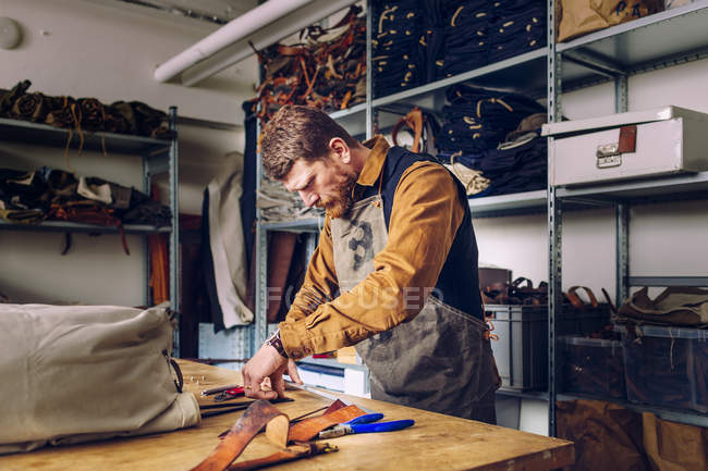 Мужчина на фабрике сумок — стоковое фото